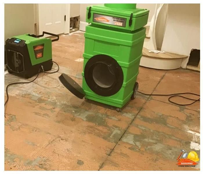 dehumidifier and air mover placed in room to dry floor after hardwood is removed from subfloor