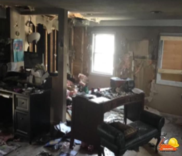 room in home with furniture, walls and debris all over room after firefighter put out fire